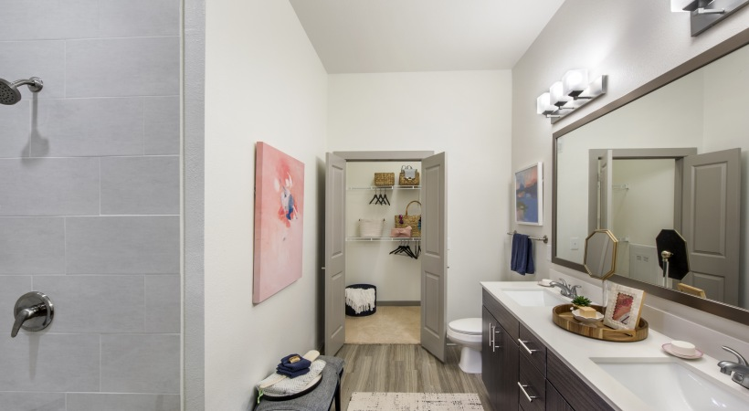 bathroom with hardwood floors and a painting on the wall and a door opening to a closet