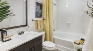 bathroom with white tiles an a yellow curtain and towels