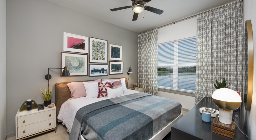 bed with a blanket and pillows with paintings hanging above and a window off to the right side with a view of the water
