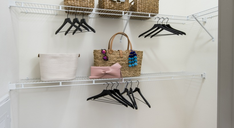 baskets and hangers on a while shelf in a closet