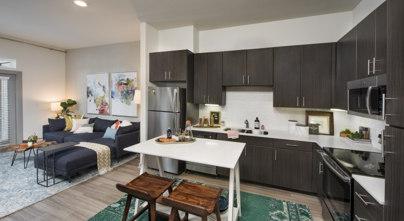 kitchen with dark brown cabinets a stainless fridge, a white kitchen table and two brown chairs